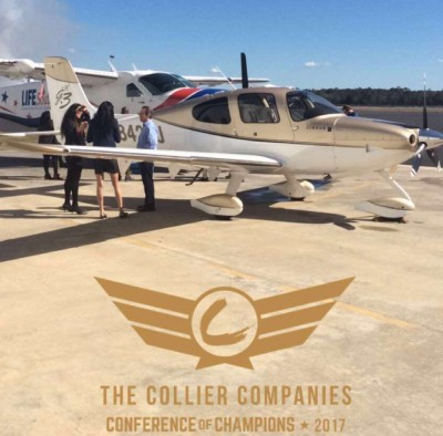 Collier empoyees stand infront of an airplane for the Collier Companies Conference of Champions