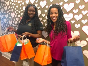 Two collier employees holding orange and blue bags of promotional items.