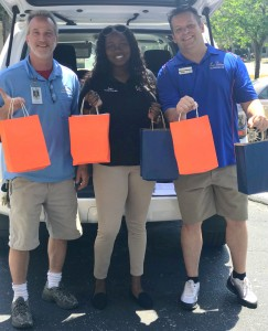 Collier employees showcasing bags of promotional items from the trunk of a van.