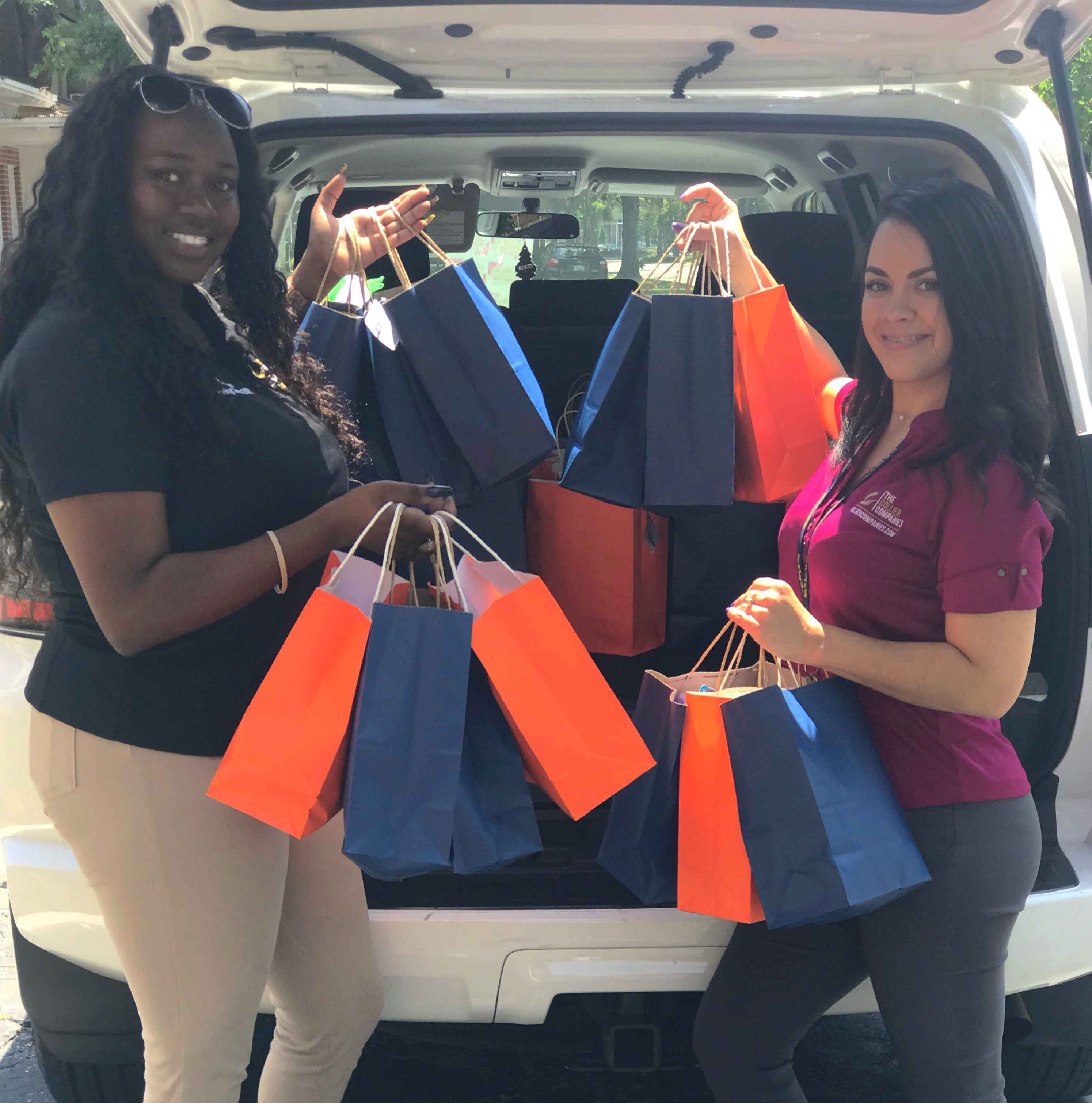 Collier employees showcasing orange and blue bags of promotional items.