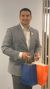 A team member smiles and holds a blue and an orange bag.