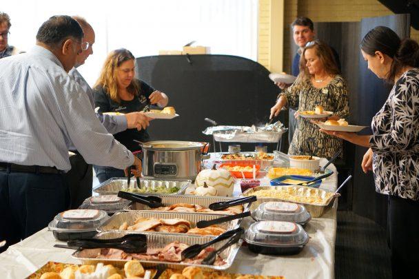 TCC Team Members gather around to prepare their plates