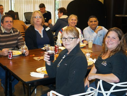 TCC Team Members smile as they enjoy a Thanksgiving potluck meal