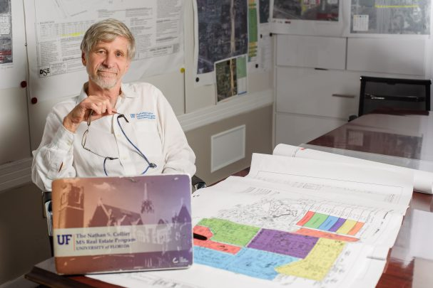 Owner, Nathan S. Collier, sits among development plans holding his glasses