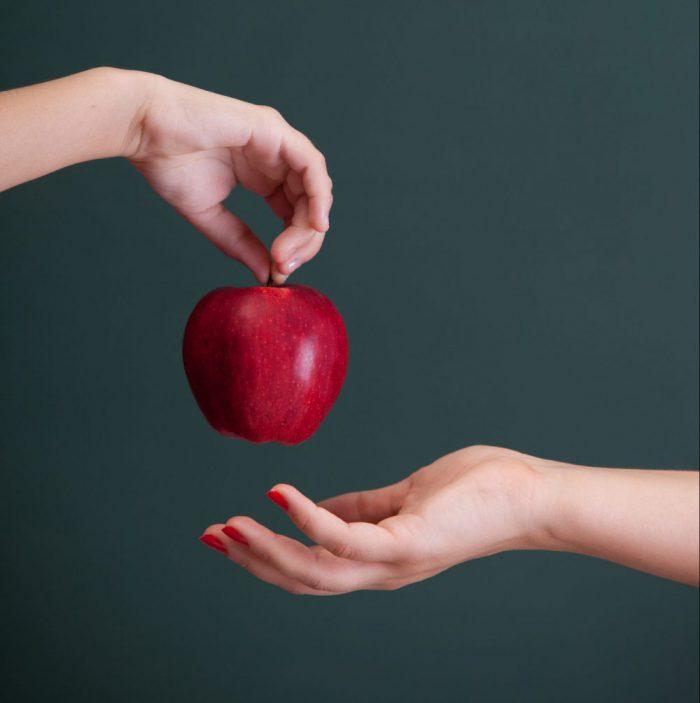 Little student hand giving apple to teacher